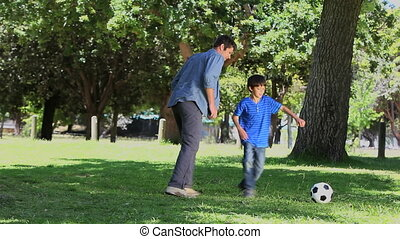 Son and his father playing football