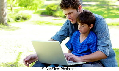 Son and his father using a laptop