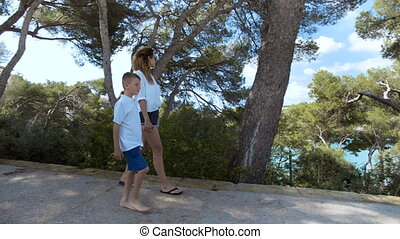 Son and mother are walking in the park near the sea