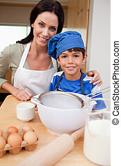 Son and mother preparing cake