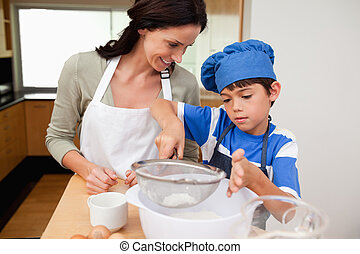 Son and mother preparing dough