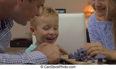 Son and parents playing with plasticine - Young parents and...