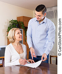 Son and senior mother with documents