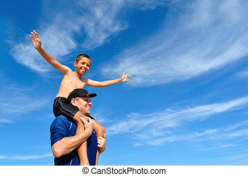 Son balancing on dad's shoulders