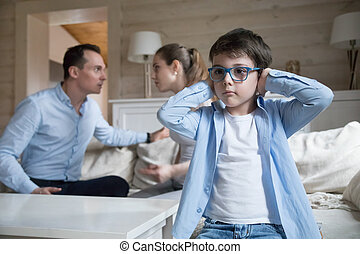 Son cover his ears with hands while parents quarreling