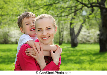son embraces behind mother for neck in park in spring