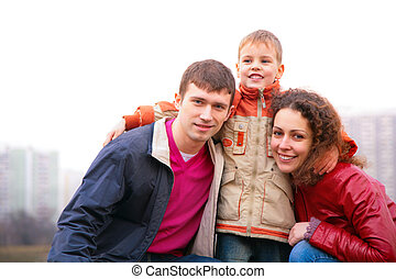 son embraces parents outdoor in city
