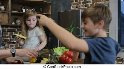 Son Filming Video Of Parents And Sister Cooking In Kitchen On Cell Smart Phone Happy Family Together At Home Preparing Food