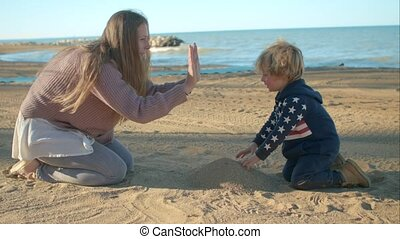 Son gives five to his mother on the beach