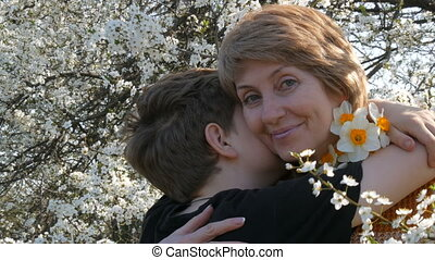 Son gives flowers to his mother. Mom and son against the...