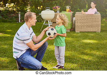 Son giving ball to father