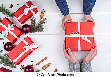 Son giving christmas gift to mum, top view. Holidays, present, childhood and happiness concept. Close up of child and mother hands with gift box on white background. Christmas family traditions