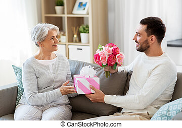 son giving present and flowers to senior mother