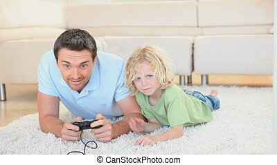 Son grabbing the joystick from his father hands while lying...