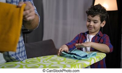 Son helping dad to fold ironed clothes at home - Positive...
