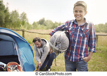 Son helping his father on camping