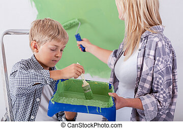 Son helping his mother painting a wall