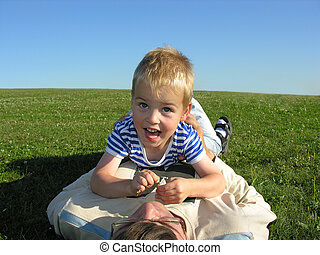 son lie on ather on green grass