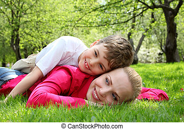 son lies on back of mother lying on grass in park in spring