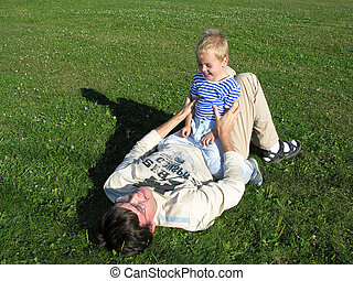 Son on father lie on grass