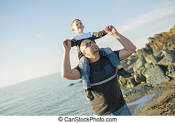Son on father shoulders at the beach having fun  sunset together