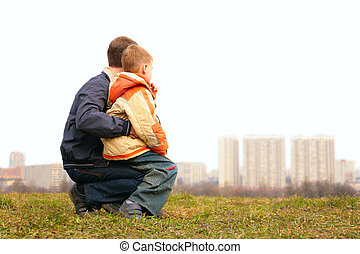 son on lap of father outdoor in city