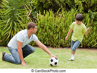 Son playing football with his fathe
