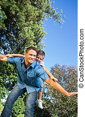 Son playing with his dad outside in the park on a summers...