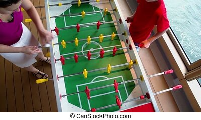 Son plays table football with mother, view from above
