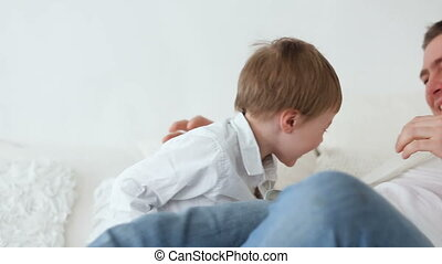 son plays with dad at home on the bed