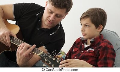 Son says that he got it while his father teaches him to play guitar close up view slow motion