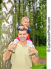 son sits on shoulders at father