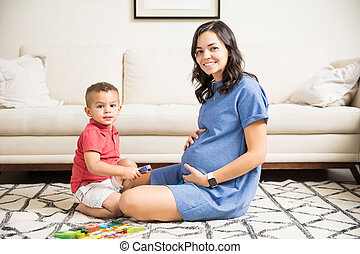 Son Sitting By Happy Mother Holding Pregnant Belly At Home