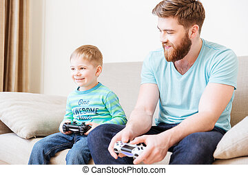 Son sitting on couch and playing computer games with father