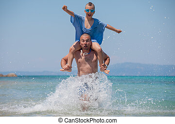 Son Splashes Father Shoulders Fun Sea