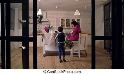 Son surprising mother with flowers in kitchen - Festively...