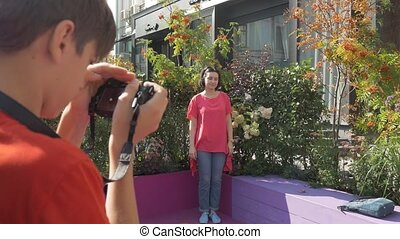 Son takes pictures of his mother on a walk, among flowers
