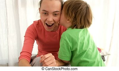 Little boy in green t shirt telling secrets to the mother's ear cheerful woman while spending time at home together