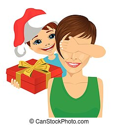 son wearing santa hat giving to mother christmas gift covering her eyes with his hand