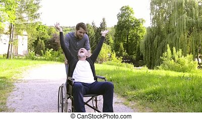 Son with disabled father in wheelchair in the park.
