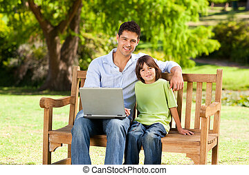 Son with his father looking at their laptop