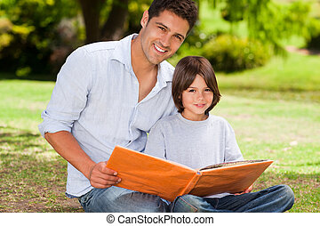 Son with his father looking at their album photo