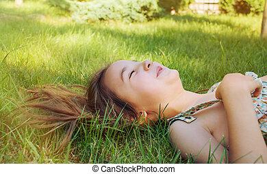 sonreír feliz, niña, mentira en la hierba, en, soleado, día de verano