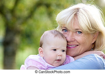 sonriente, abuela, teniendo bebé