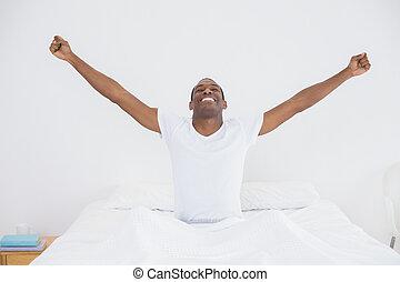 sonriente, afro, hombre, extensión, el suyo, brazos hacia fuera, en cama