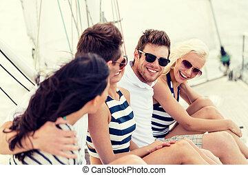 sonriente, amigos, sentado, en, yate, cubierta