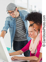 sonriente, artistas, trabajar en computadora, en, oficina