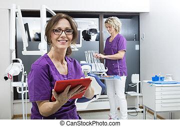 sonriente, ayudante, tenencia, tableta de digital, mientras, colega, trabajando