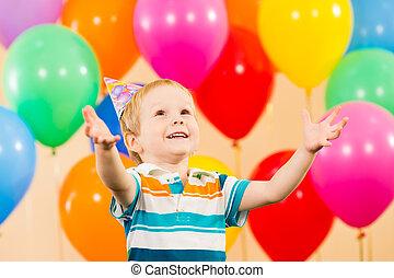 sonriente, chico niño, con, globos, en, fiesta de cumpleaños