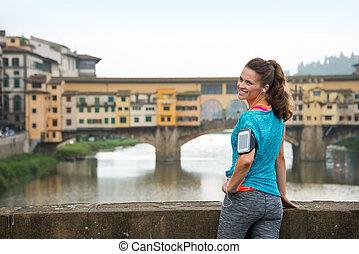 sonriente, condición física, mujer estar de pie, delante de, ponte vecchio, en, flor